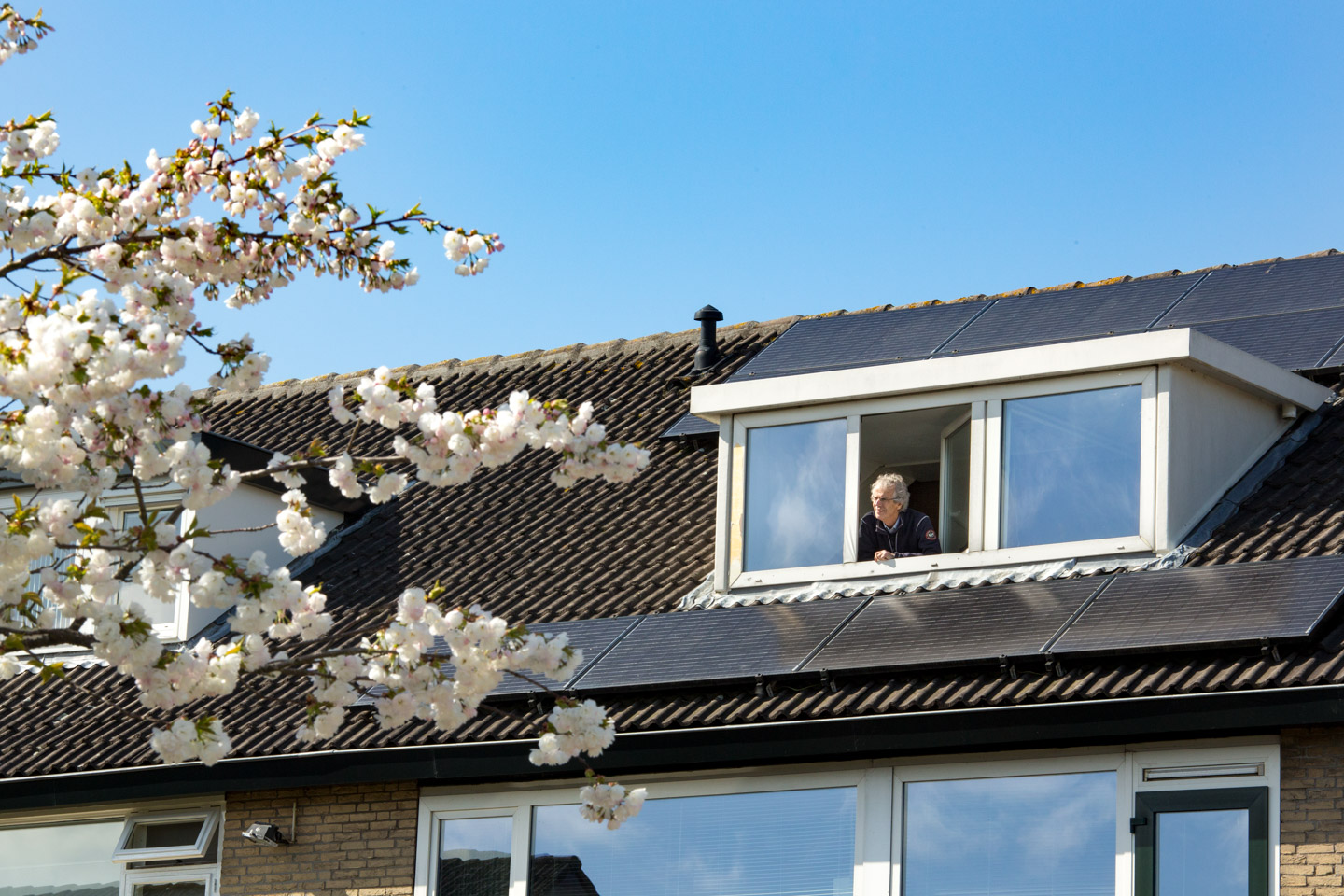 Man is enjoying the sunlight in spring that also gives energy to his solar panels